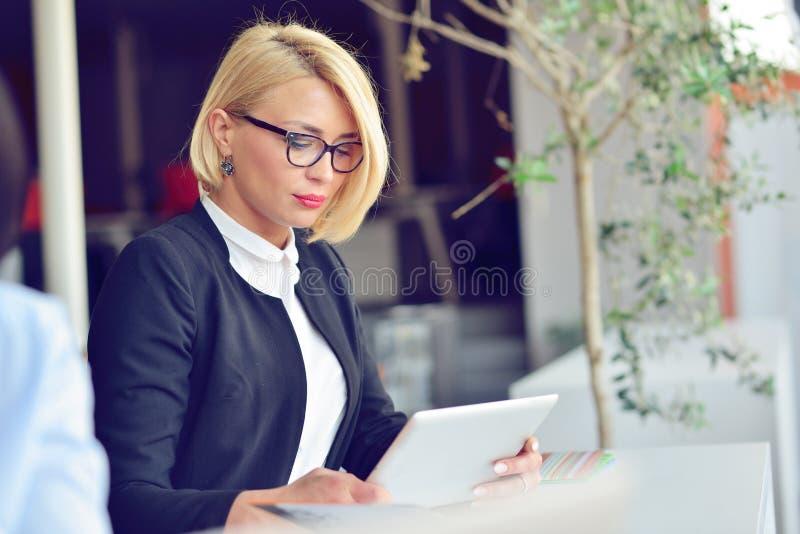 Ritratto del primo piano del computer portatile attivo della tenuta della donna di affari mentre stando all'ufficio fotografie stock libere da diritti
