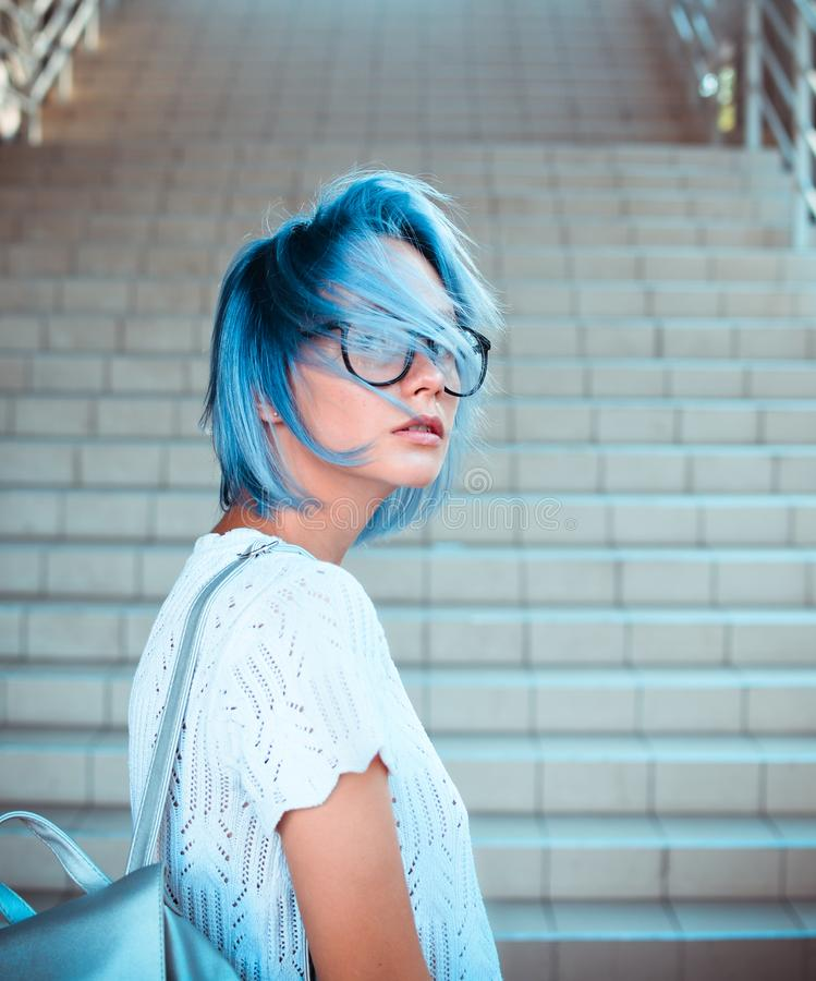 Ritratto del primo piano dei vetri d'uso di una ragazza dei pantaloni a vita bassa con capelli blu Bellezza atipica Modo della vi fotografia stock