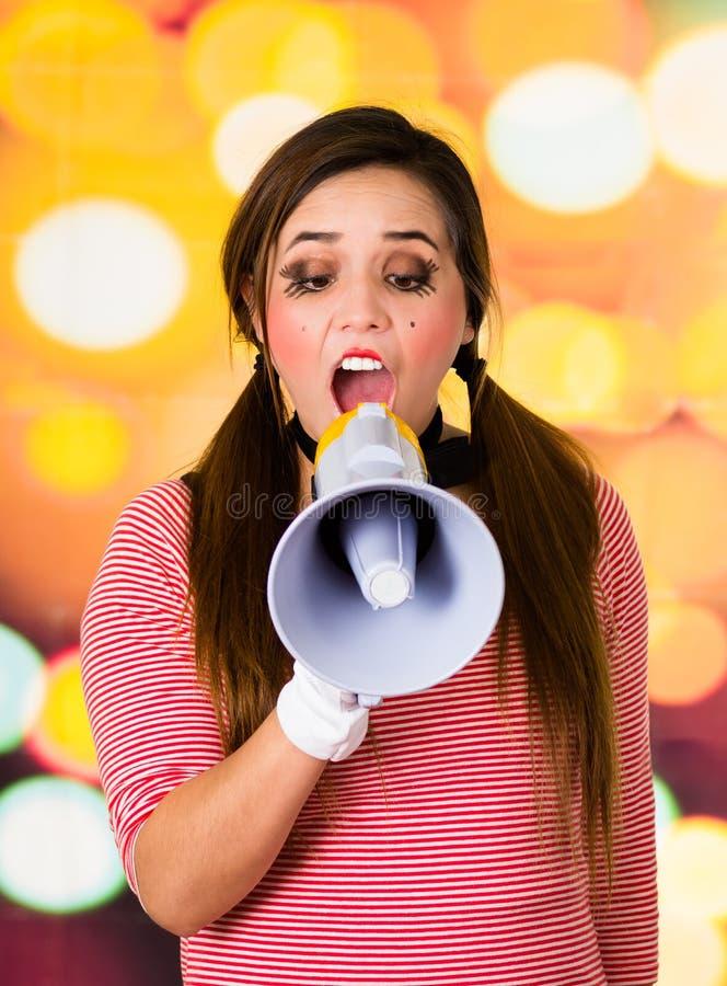 Ritratto del primo piano del mimo femminile del pagliaccio che grida con un megafono immagine stock