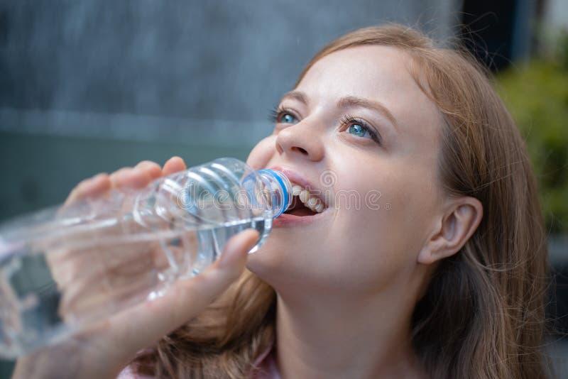 Ritratto del primo piano dell'acqua potabile della giovane donna caucasica da una bottiglia di plastica fotografie stock libere da diritti