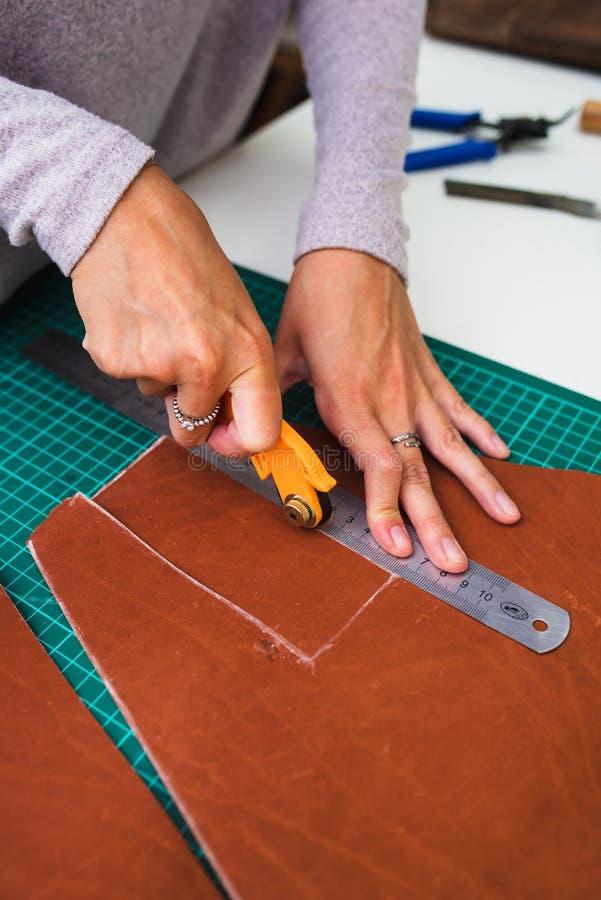 Ritratto del primo piano dell'artigiano di cuoio irriconoscibile che lavora facendo i measupenets nei modelli alla tavola nello s fotografie stock libere da diritti