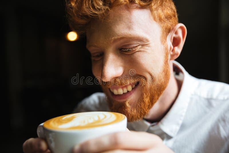 Ritratto del primo piano dell'assaggio barbuto sorridente dell'uomo del readhead riccio fotografia stock libera da diritti