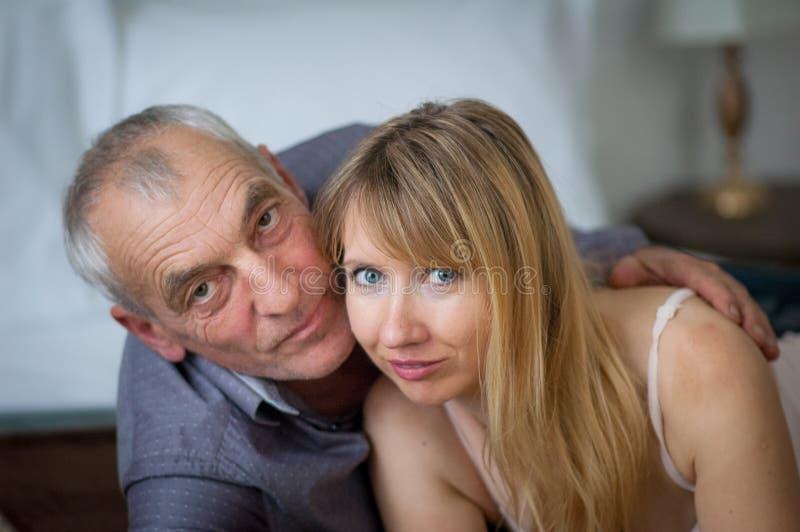 Ritratto del primo piano dell'uomo anziano che abbraccia la sua giovane moglie in biancheria sexy che si trova a letto nella loro immagine stock