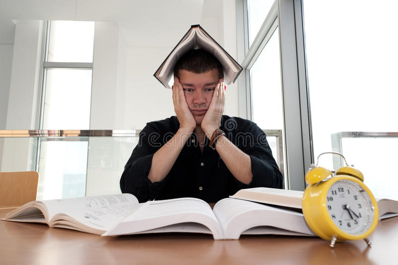 Ritratto del primo piano dell'uomo bianco circondato dalle tonnellate di libri, sveglia, sollecitata dal termine di progetto, stu fotografia stock