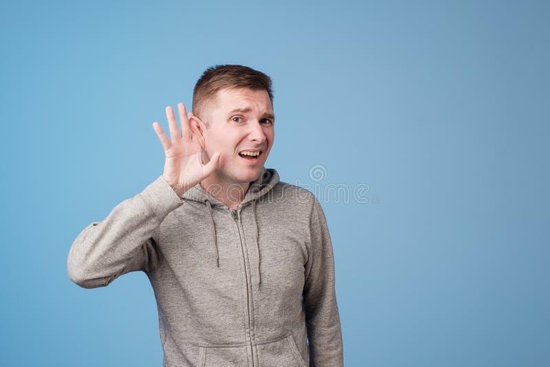 Ritratto del primo piano dell'uomo europeo che dispone mano sull'orecchio che ascolta con attenzione il gossip isolato su fondo b fotografia stock libera da diritti