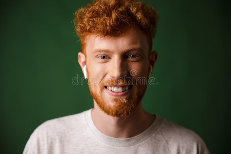 Ritratto del primo piano dell'uomo riccio sorridente della testarossa, ascoltante il mus fotografie stock libere da diritti