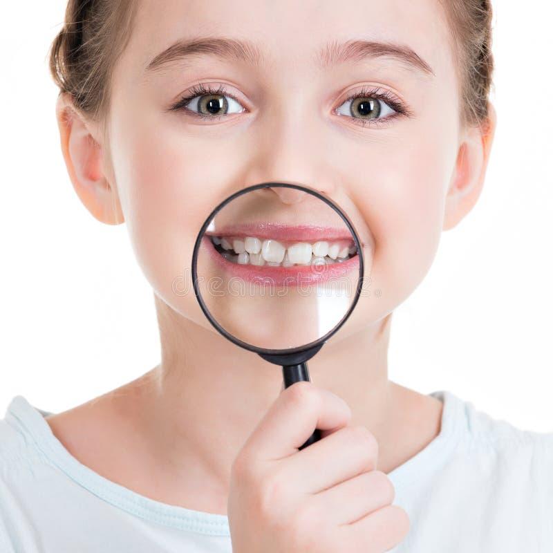 Ritratto del primo piano della bambina che mostra i denti con un ingrandimento fotografia stock