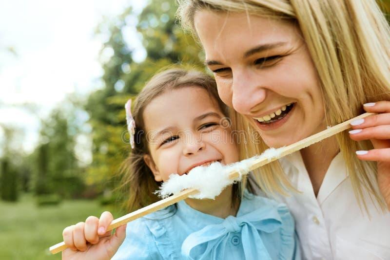 Ritratto del primo piano della bambina felice divertendosi e mangiando zucchero filato con sua madre nel parco fotografie stock