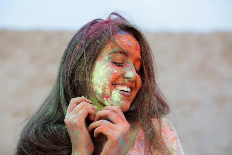 Ritratto del primo piano della donna castana emozionale che celebra festival di colori di Holi al deserto immagini stock