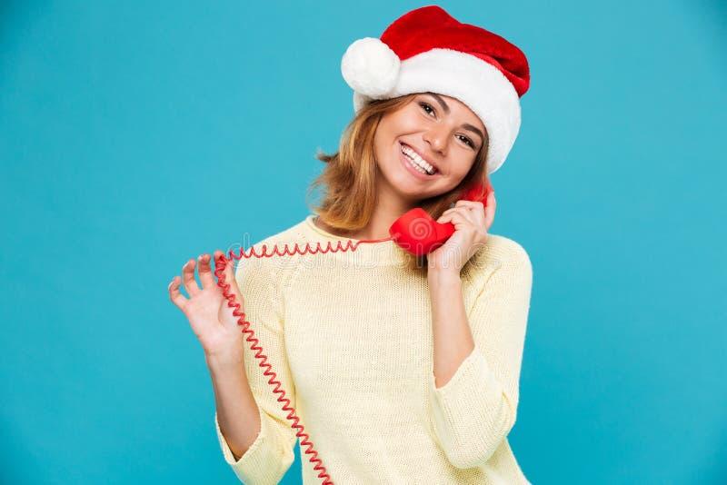 Ritratto del primo piano della donna castana sveglia in cappello del ` s di Santa che parla sul retro telefono, esaminante macchi fotografie stock