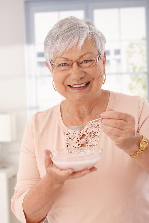 Ritratto del primo piano della donna felice che mangia i cereali immagini stock