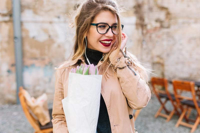 Ritratto del primo piano della giovane donna adorabile alla data nel caffè all'aperto che tiene i bei fiori Ragazza incantante co fotografia stock libera da diritti
