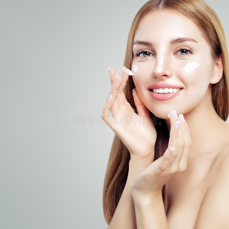 Ritratto del primo piano della giovane donna allegra con pelle sana che applica la crema di giorno immagini stock libere da diritti