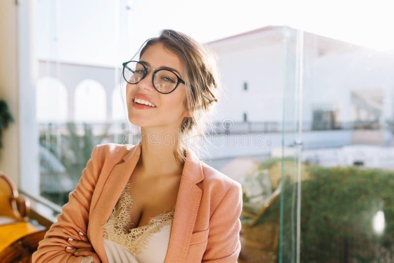 Ritratto del primo piano della giovane donna che indossa i vetri alla moda, signora astuta in rivestimento rosa elegent con la bl fotografia stock
