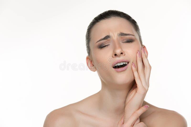 Ritratto del primo piano della giovane donna che soffre dal dolore di dente terribile, toccante premendo la sua guancia Cure odon immagine stock