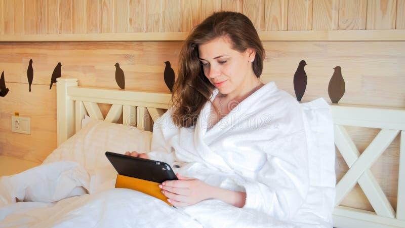 Ritratto del primo piano della giovane donna sorridente che si trova a letto e che lavora al computer della compressa fotografie stock