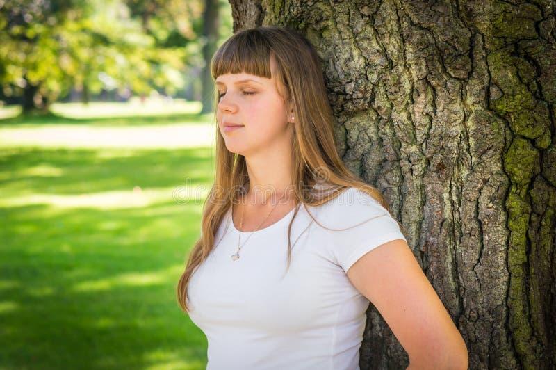 Ritratto del primo piano della giovane donna vicino all'albero immagine stock