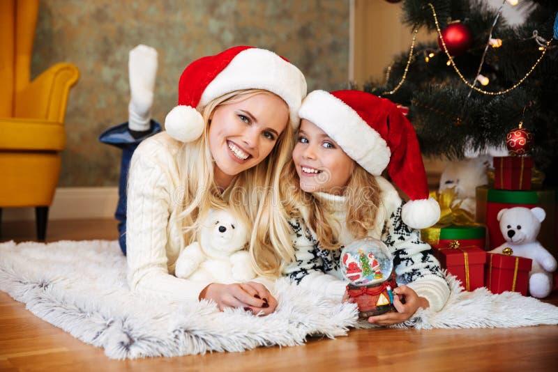 Ritratto del primo piano della madre e della figlia bionde felici nel ` s di Santa fotografia stock
