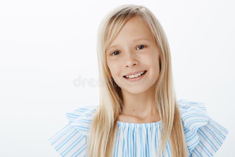 Ritratto del primo piano della ragazza bionda adorabile piacevole in blusa blu, sorridente allegramente e guardante fisso alla ma immagine stock libera da diritti
