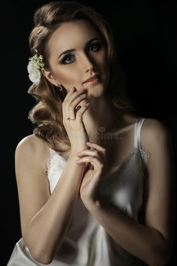 Ritratto del primo piano della ragazza con capelli biondi e le mani vicino al fronte Sposa con bello trucco su un fondo scuro fotografie stock libere da diritti