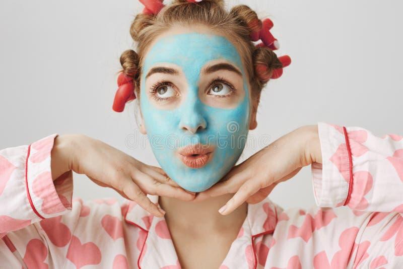 Ritratto del primo piano della ragazza girly europea con l'espressione sveglia, i pigiami d'uso ed i capelli-bigodini, stanti con fotografia stock libera da diritti