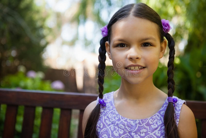 Ritratto del primo piano della ragazza sorridente che si siede sul banco immagine stock libera da diritti