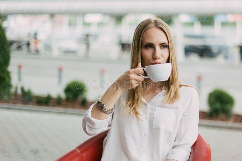 Ritratto del primo piano della tazza bevente della donna bionda seria di tè nel caffè fotografia stock