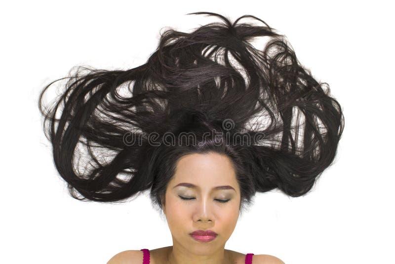 Ritratto del primo piano delle donne asiatiche lunatiche che si trovano sulla terra con capelli lunghi neri ribaltamento sostitut immagini stock