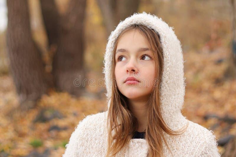 Ritratto del primo piano di bella bambina di sogno premurosa in cappotto bianco di maglia con cappuccio che resta nella foresta d fotografia stock