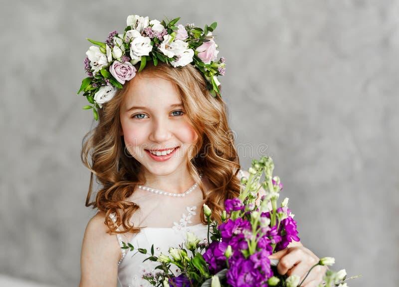 Ritratto del primo piano di bella bambina sveglia in una corona dei fiori freschi sulla sua testa ed in un canestro di bella moll fotografia stock