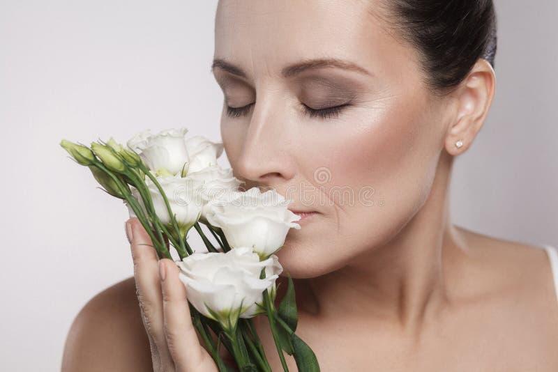 Ritratto del primo piano di bella donna allegra con pelle perfetta e le grinze invecchiate che odorano i fiori Concetto di cura d immagini stock libere da diritti