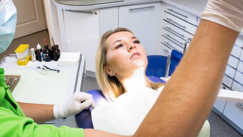 Ritratto del primo piano di bella donna bionda che si trova nella sedia del dentista alla clinica moderna immagine stock libera da diritti
