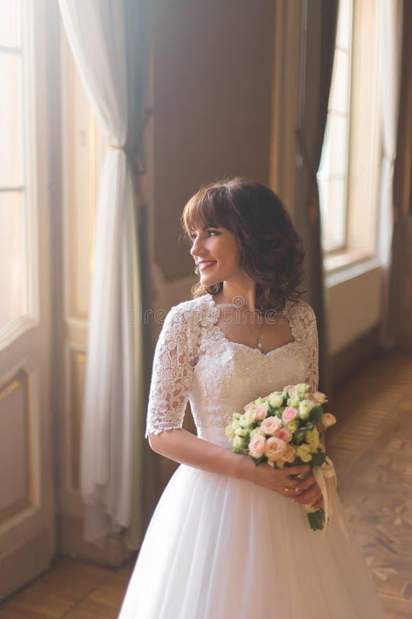 Ritratto del primo piano di bella donna che osserva verso nel vestito da sposa vicino alla finestra l'interno di lusso fotografie stock