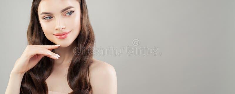 Ritratto del primo piano di bella donna con chiara pelle che sorride e che guarda da parte sul fondo grigio dell'insegna fotografia stock libera da diritti