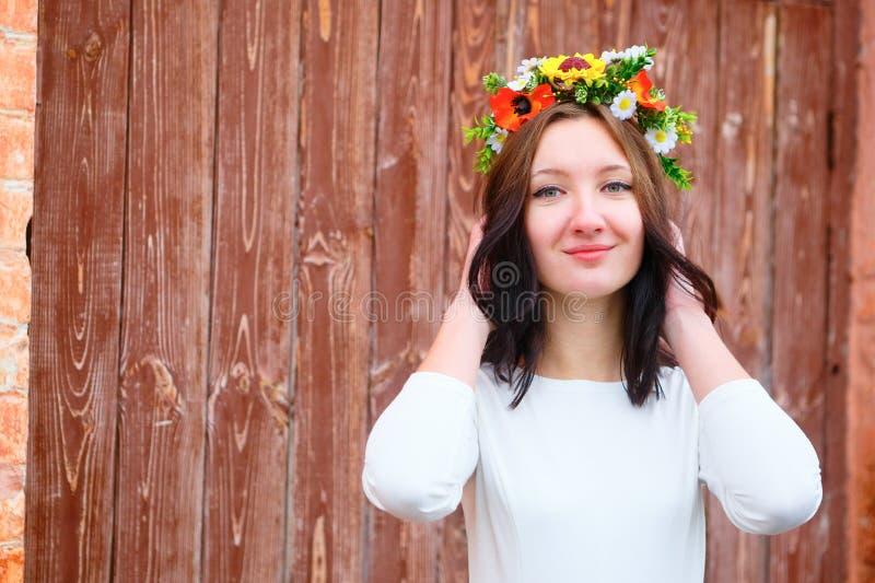 Ritratto del primo piano di bella donna di sorriso dei giovani con la corona del fiore sulla sua testa vicino alla porta di legno fotografia stock