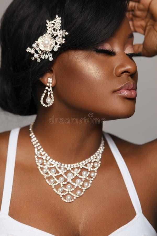 Ritratto del primo piano di bella donna nera della pelle Giovane sposa incantante in vestito da sposa e gioielli immagini stock
