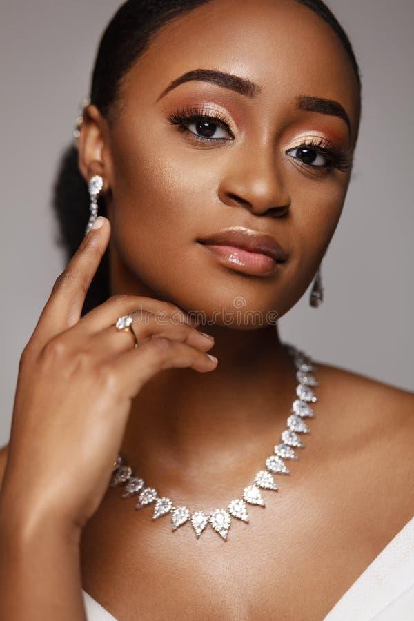 Ritratto del primo piano di bella donna nera della pelle Giovane sposa incantante in vestito da sposa e gioielli immagine stock libera da diritti