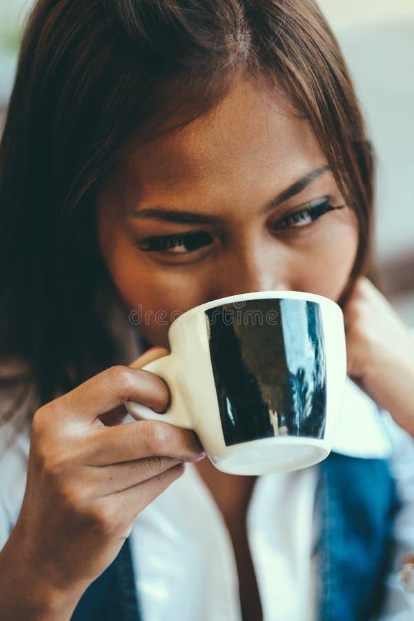 Ritratto del primo piano di bella giovane donna che tiene tazza di tè o di caffè, fuoco selettivo immagini stock libere da diritti