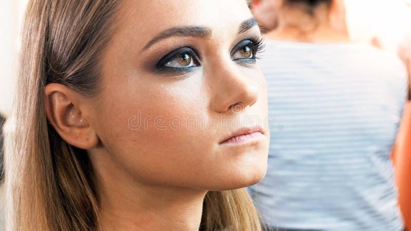 Ritratto del primo piano di bella giovane donna con gli occhi di marrone ed il trucco affumicato degli occhi fotografia stock libera da diritti