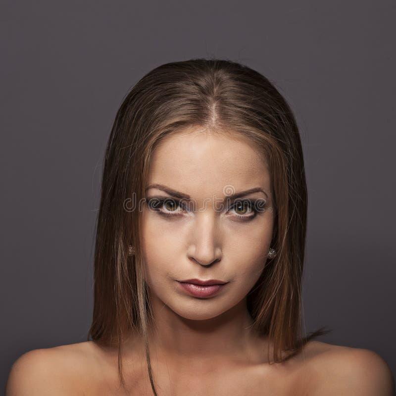 Ritratto del primo piano di bella giovane donna su fondo blu scuro fotografie stock