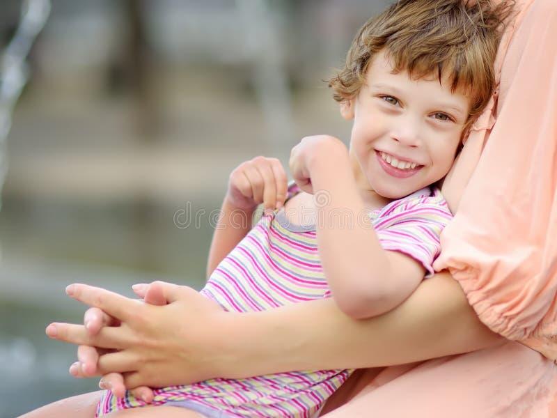 Ritratto del primo piano di bella ragazza disabile nelle armi di sua madre divertendosi in fontana del parco pubblico al giorno d immagini stock
