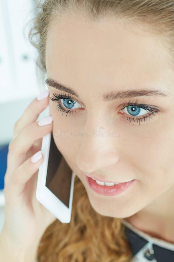 Ritratto del primo piano di bella ragazza sorridente che parla sul telefono cellulare nell'ufficio fotografia stock