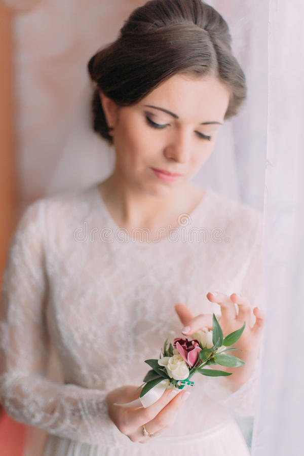 Ritratto del primo piano di bella sposa innocente in vestito da sposa vicino alla finestra che tiene boutonniere sveglio fotografia stock libera da diritti