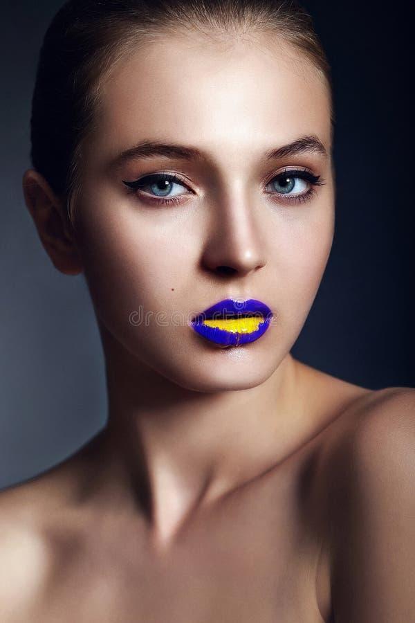 Ritratto del primo piano di fascino di bello modello alla moda sexy della giovane donna con trucco luminoso, con giallo blu lumino immagine stock