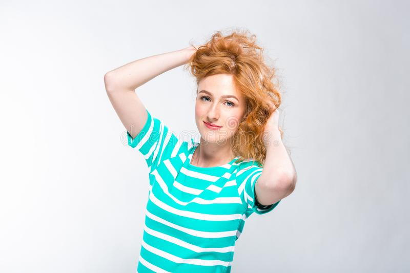 Ritratto del primo piano di giovane, bella donna con capelli ricci rossi in un vestito da estate con le strisce del blu nello stu fotografia stock