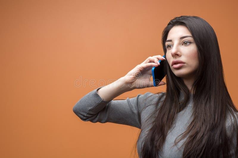 Ritratto del primo piano di giovane bella donna pensierosa castana che tiene il suo smartphone e che ascolta, pensante a qualcosa fotografia stock
