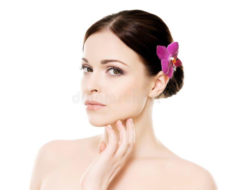 Ritratto del primo piano di giovane, bella e donna in buona salute con un fiore dell'orchidea immagine stock