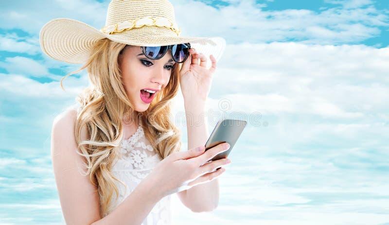 Ritratto del primo piano di giovane bionda che per mezzo di uno smartphone fotografie stock libere da diritti