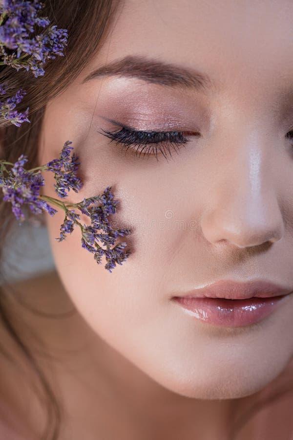 Ritratto del primo piano di giovane castana attraente e bello Sguardo fresco della molla con i fiori immagine stock libera da diritti