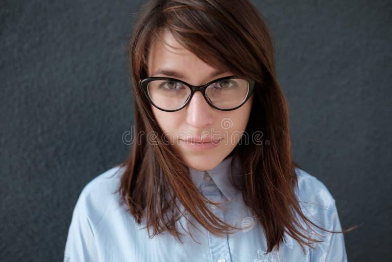 Ritratto del primo piano di giovane donna attraente con i vetri su un fondo scuro fotografie stock libere da diritti